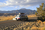 Van with luggage rack on highway leading into Great Sand Dunes National Park, Colorado. John offers private photo trips to Great Sand Dunes National Park and all of Colorado. All year long.