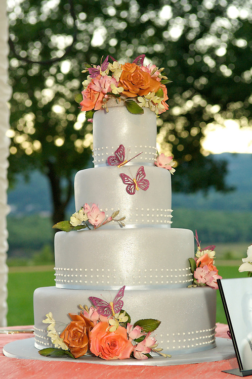 Still life photo of the wedding cake decorated with flowers and butterflies.