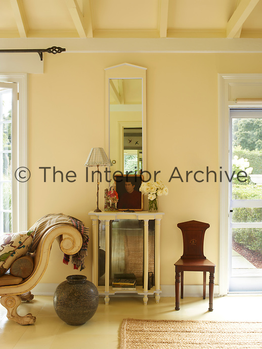 In the yellow living room, a mirror hangs above a glass display cabinet; an Empire style sofa stands to one side.