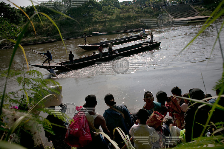 After less than three days in Thailand the Burmese refugees begin to return back across the Moe Me river to Burma. An estimated 20,000 had fled into Thailand to escape clashes in the border towns of Myawaddy and Pyaduangsu, only a day after a Burmese election which critics described as a sham..Ethnic minorities along the Thai-Burma border had warned earlier that the junta would launch a major offensive after the election, as many armed rebel groups had refused to become part of the government-controlled Border Guard Forces.