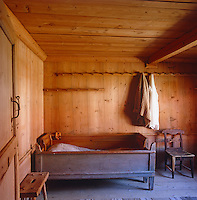 An expandable cot bed stands in the corner of this bedroom in which rows of pegs are used Shaker style to hang clothes