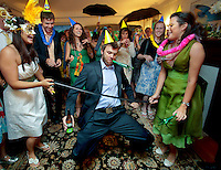 Beer in hand, a guest does the limbo under a belt during a intimate party following a Seattle wedding. (Photo by Dan DeLong/Red Box Pictures)