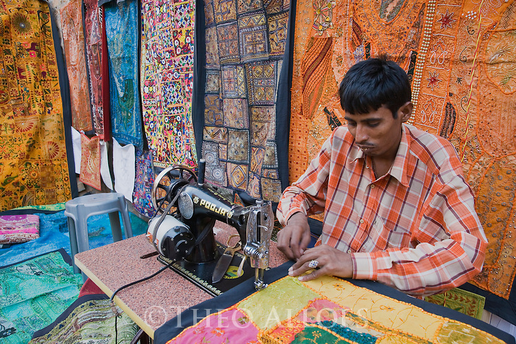 Male seamstress working on sewing machine producing colorful wall hangings with beautiful fabric, Jaisalmer, Rajasthan, India --- Model Released