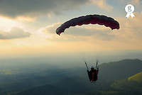 Young man paragliding off hill, rear view (Licence this image exclusively with Getty: http://www.gettyimages.com/detail/200482373-001 )