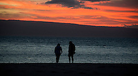 Two unidentified people on the beach at sunset looking towards the Hawaiian island of Lanai from Kaanapali Beach, Maui, Hawaii on Thursday, February 23, 2017.  Most of Lanai is owned by the tech billionaire Larry Ellison, who purchased it in 2012. Photo Credit: Ron Sachs/CNP/AdMedia