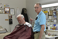 """4/8//16 Canton, MS. With a straight razor and towel in hand barber Bobby Chandler says he will not serve any LGBT people. Days after Mississippi Governor Phil Bryant  signed a controversial """"religious freedom"""" bill into law, Bobby Chandler of Chandler O'Cain barber shop in Canton Mississippi says he will not  serve any LGBT people. Mr. Chandler pictured in a blue shirt working on a customer has been in business in the same space for over 30 years.  Danny O'Cain Chandlers business partner is pictured on the right in the pink shirt. Photo ©Suzi Altman"""