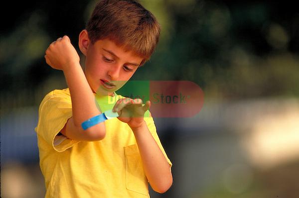 serious young boy bandaging injured elbow