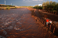 John and Diana Hess enjoy sunset beneath the Campbell bridge along the raging Rillito Wash..A fast moving storm hit Tucson late afternoon depositing rain, down trees and power lines.throughout the city. The raging torrent was a beacon to residents coming out to enjoy a cooler.wetter look at the familiar dry wash.