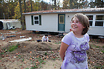 Christina Hall (right), 11, arrives at her family's new trailer home after being homeless for two and a half months.