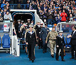 Armed forces personnel march out to take the applause of the fans at half-time