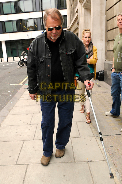 DAVID SOUL .Leaving BBC Radio 2, England, UK..May 16th 2011.full length jeans denim black jacket cane sunglasses shades walking looking down.CAP/IA.©Ian Allis/Capital Pictures.