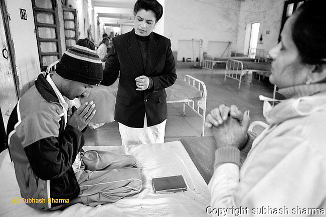 Sister Massey lends support to a MDR-TB patient as he reads from the Bible