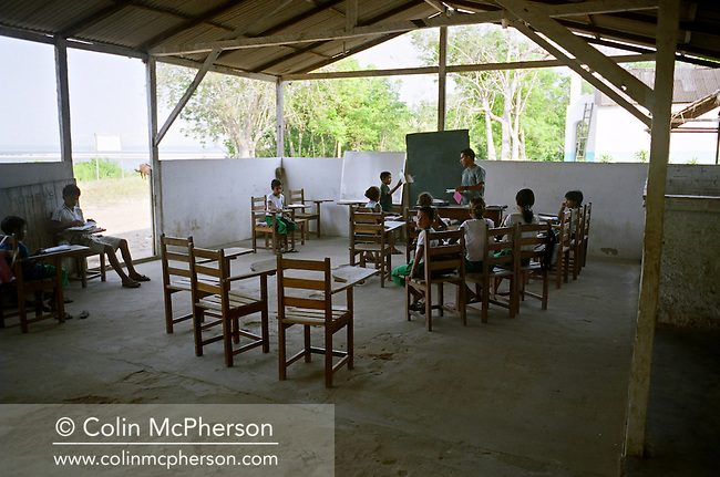A teacher giving a lesson to pupils at the primary school at Jaguarari. The Floresta Nacional do Tapajos (FLONA), a 6500 km2 protected reserve, was home to several small communities which lived on the banks of the Rio Tapajos river. The communities did not have electricity or running water and access to the villages was by unpaved dirt roads from Santarem and Highway BR163.