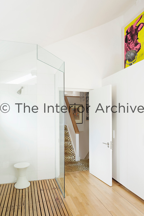 The bathroom is simple with a glass walk-in shower and walls of storage double up as gallery space.