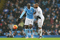 Yaya Toure tussles over the ball with Ashley Williams during the Barclays Premier League Match between Manchester City and Swansea City played at the Etihad Stadium, Manchester on 12th December 2015