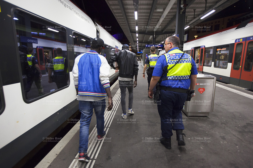 Switzerland. Canton Ticino. Locarno. Railway station. Two police officers from TPO (Transport Police) have controlled inside a TILO train two african men from Ghana with no valid train tickets.The policemen and both african men walk on the platform and go to control their identities at the police station. Both black men are migrants in an irregular situation (illegal migrants) in Switzerland and don't have any valid legal identity document. They will be arrested by the police officers and transferred later in the night to the borders guards. An identity document (also called a piece of identification or ID, or colloquially as papers) is any document which may be used to prove a person's identity. TPO (Transport Police) is the Swiss Federal Railways Police. Swiss Federal Railways (German: Schweizerische Bundesbahnen (SBB), French: Chemins de fer fédéraux suisses (CFF), Italian: Ferrovie federali svizzere (FFS)) is the national railway company of Switzerland. It is usually referred to by the initials of its German, French and Italian names, as SBB CFF FFS. TILO (Treni Regionali Ticino Lombardia) creates efficient train connections between the towns in the canton Ticino. 23.07.2017 © 2017 Didier Ruef