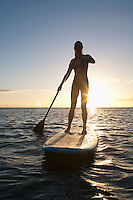 A female standup paddler with a sunstar at sunset, Maui.