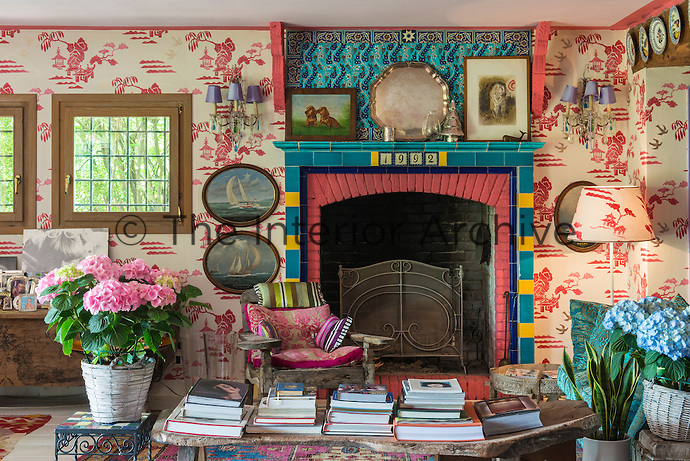 The walls of the living room are covered in a Chinoiserie-style wallpaper and the bricks around the fireplace have been painted in a patching pink, framed by a turquoise ceramic tiled mantelpiece