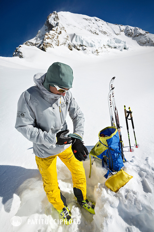 Ueli Steck getting his gear and clothing organized after skiing from the Jungfraujoch to the base of the Mönch for a climbing training day, Switzerland.