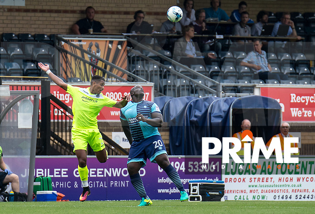 Adebayo Akinfenwa of Wycombe Wanderers and Richard Brindley of Colchester United during the Sky Bet League 2 match between Wycombe Wanderers and Colchester United at Adams Park, High Wycombe, England on 27 August 2016. Photo by Liam McAvoy.