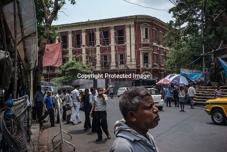 Commuters wait for public transport next to the Writers Building, the secretariat building of the State Government of West Bengal in BBD Bagh in Kolkata, West Bengal  on Friday, May 26, 2017. Photographer: Sanjit Das