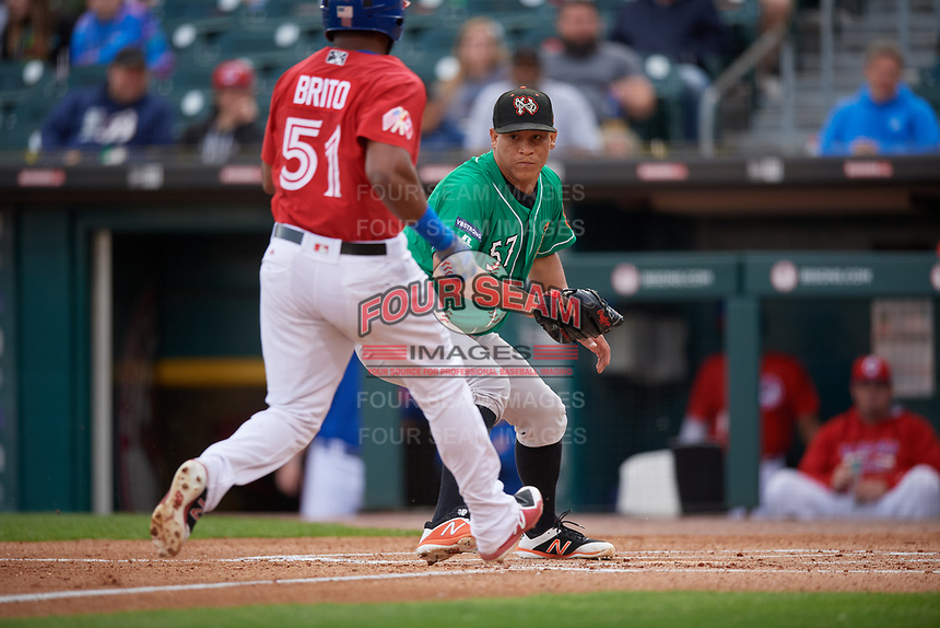 Norfolk Tides pitcher Luis Ysla (57) looks to tag Socrates Brito (51) during an International League game against the Buffalo Bisons on June 21, 2019 at Sahlen Field in Buffalo, New York.  Buffalo defeated Norfolk 1-0, the second game of a doubleheader.  (Mike Janes/Four Seam Images)