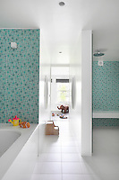 A spacious turquoise and white bathroom with a shower room and seperate bathing area adjoins the children's bedroom