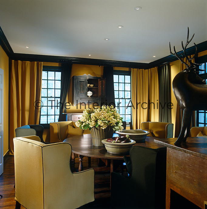 In this dining room an air of intimacy has been created with floor-to-ceiling curtains in yellow ochre and khaki matching the generously proportioned and upholstered wing-back chairs around the table