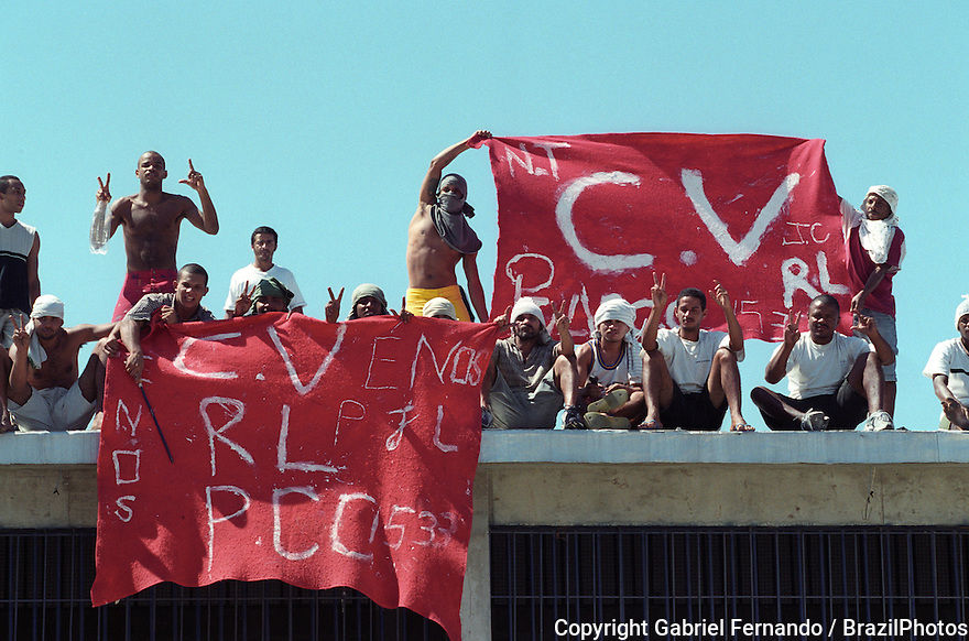 "Rebellion in reformatory prison, Rio de Janeiro, Brazil. Penitentiary revolt, mutiny, insurrection. Prisoners from criminal faction ""Comando Vermelho"" or CV ( Red Command ) hold the faction flag on the penitenciary roof. Violence, delinquents, outlaws."
