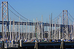 MOORED SAILBOAT MASTS BLEND WITH OAKLAND's BAY BRIDGE in BACKGROUND