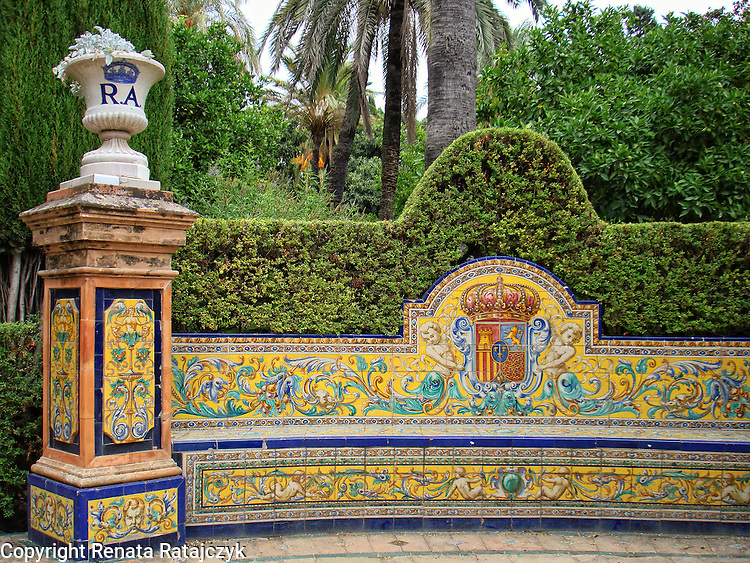 A bench in Royal Gardens in Seville, Spain. It is beautifully decorated with colourul ceramics with angles and floral design.