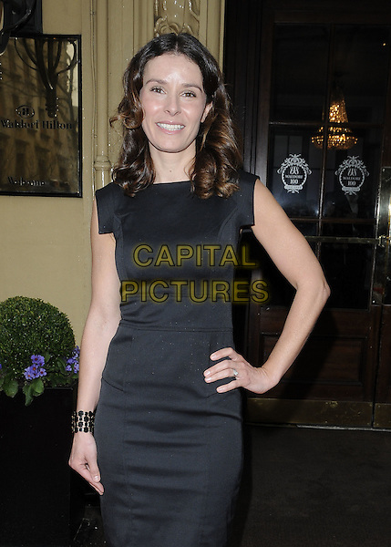 TANA RAMSAY.Tesco Magazine Mum Of The Year .Awards 2010, held at The Waldorf Hilton Hotel, Aldwych, London, England, UK,.February 28th 2010..Arrivals half length black dress hand on hip cuff bracelet smiling .CAP/CAN.©Can Nguyen/Capital Pictures