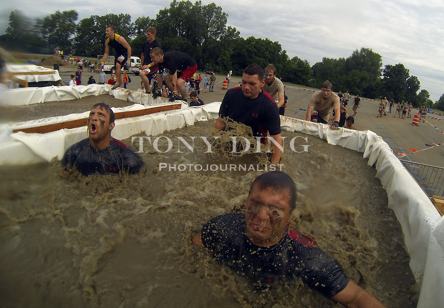 "16 April 2010: Competitors jump into a deep ice water tub called the ""Arctic Enema"" and have to dive under a bar in one of twenty obstacles in the Tough Mudder adventure endurance race at Michigan International Speedway in Brooklyn, Michigan."