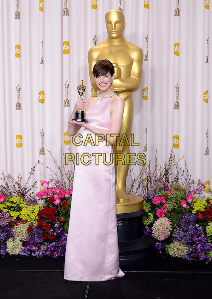 Anne Hathaway (wearing Prada).85th Annual Academy Awards held at the Dolby Theatre at Hollywood & Highland Center, Hollywood, California, USA..February 24th, 2013.pressroom oscars full length pink sleeveless silk satin dress award trophy winner .CAP/ADM/RE.©Russ Elliot/AdMedia/Capital Pictures.