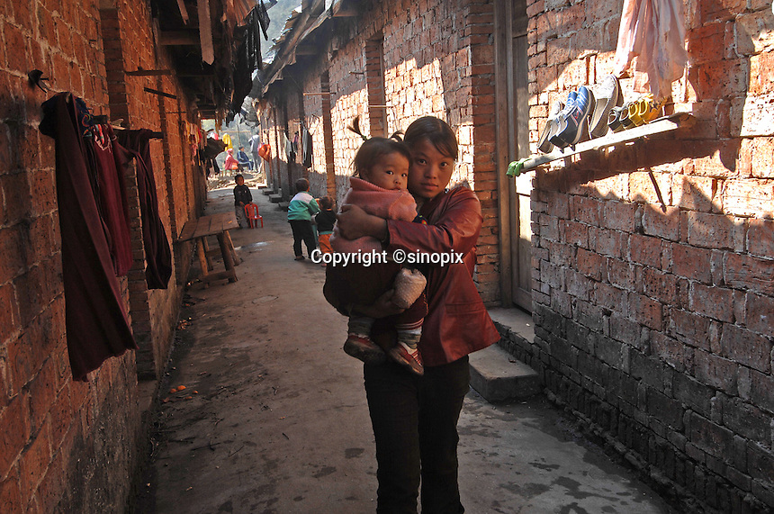 "Tao Ming Xu, 20 and her 6 month old baby in  the dormatories at The Tian Hu (Sky Lake) Tea Farm in the mountains outside Fuding City, Fujian Province where ""Silver Tip"" tea is produced.  Workers here are paid around 53 pounds a month during harvest season, they work ten hour days, seven days a week and the women work with the children strapped to their backs. The tea sells for upto 20 pounds a pot in the UK."