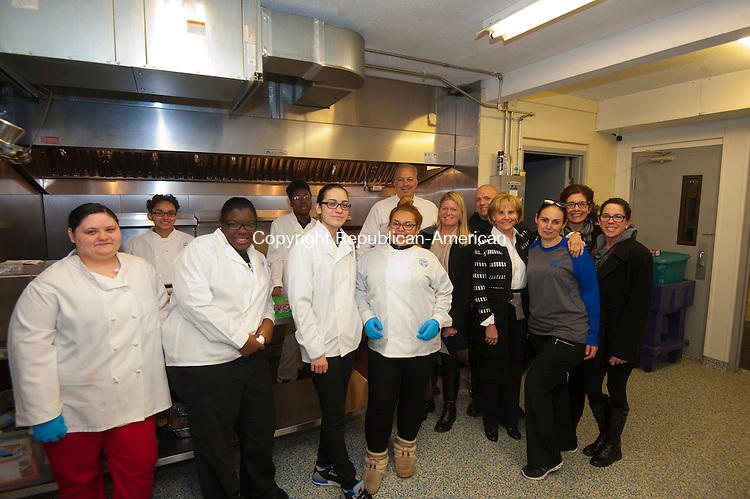 WATERBURY,  CT-122016JS13 --Members of the Elisha Leavenworth Foundation along with PAL officers and students in the PAL culinary training program, pose for a photo inside the kitchen of the PAL building in Waterbury on Tuesday. The Elisha Leavenworth Foundation donated more than $34,000.00 to help fund the culinary  training program. Jim Shannon Republican American