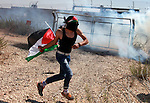 A Palestinian protester throws stones at Israeli border police during clashes after a protest against Israel's separation barrier and in solidarity with Palestinian prisoners being held in Israeli jails, in the West Bank village of Bilin near Ramallah August 30, 2013. Photo by Issam Rimawi