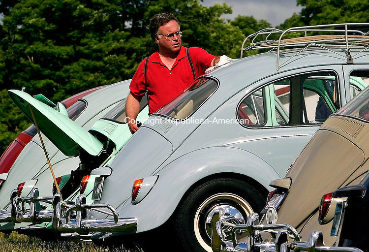 HARWINTON, CT - 19 JUNE 2005 -061905JS01--Gary Bok of Hope Valley, Rhode Island wipes down his 1967 VW Beatle during his first time visit to the 17th annual Litchfield Bug in held Sunday at the Harwinton Fairgrounds. Proceeds from the event will benefit the Bronc Callahan Community Fund, Inc.  --Jim Shannon Photo--Harwinton; Bronc Callahan, Gary Bok are CQ