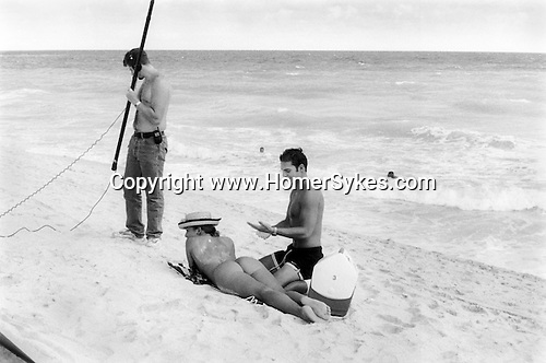 SOUTH BEACH MIAMI FLORIDA -  USA. 1999..A NAKED WOMAN LIES ON THE BEACH WITH THE SEA IN THE BACKGROUND, WHILE A YOUNG MAN IN SWIMMING SHORTS RUBS SUN OIL LOTION ONTO HER BACK, A FILM SOUND TECHNICIAN STANDS NEAR BY.