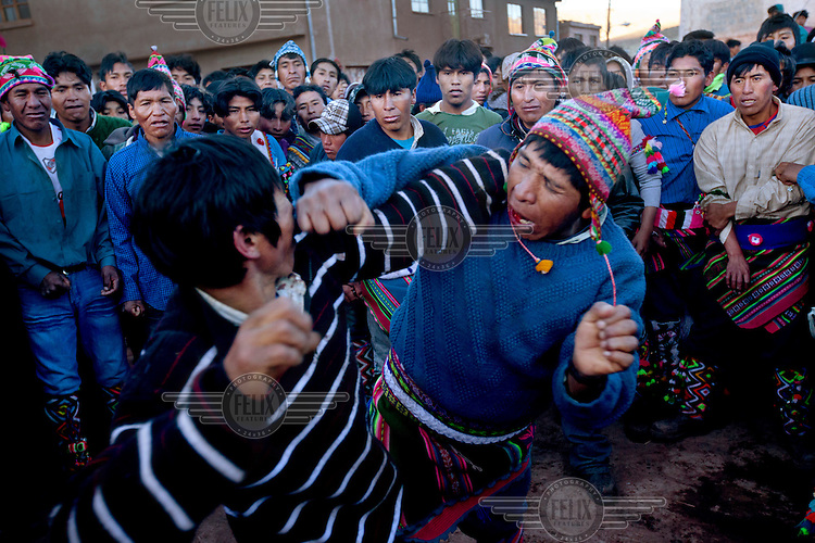 Men punch each other during the ritual fighting in the plaza of Macha. <br /> <br /> The people of Macha and surrounding communities carry on the pre-Columbian tradition of ritual fighting. The communities gather on the plaza of Macha to fight and dance in competition with each other. The blood that is spilled is an offering to Mother Earth. In return, the people ask for rain and a good harvest. This ritual is called tinku or fiesta de la cruz since the cross is also engaged in the festivities. The cross is dressed up, given offerings and brought from communities around Macha to the church in town. This syncretic festival melds pagan, pre-christian rituals with Catholic practice. /Felix Features