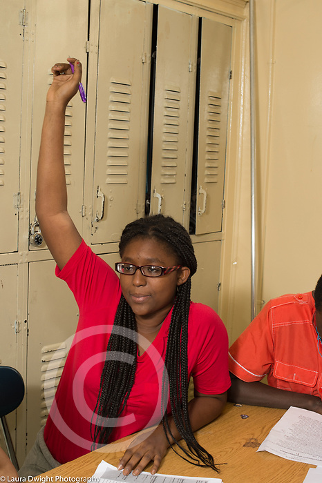 Education high school classroom scenes female student raising hand in class