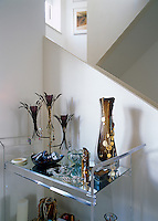 Necklaces and trinkets hang from contemporary candelabra on a mirrored Lucite trolley