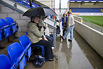 Chester City 1 Altrincham 3, 21/11/2009. Deva Stadium, Football Conference. Supporters sheltering under an umbrella in the front row of the Vaughan Stand at the Deva Stadium, Chester, home of Chester City Football Club, before kick-off in the club's Blue Square Premier fixture against Cheshire rivals Altrincham. The visitors won by three goals to one. Chester were in administration at the start of the season and were penalised 25 points before the season began. Photo by Colin McPherson.