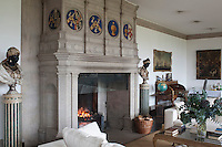 The restored carved stone fireplace, flanked by a pair of Venetian busts, is a clear focal point in the spacious drawing room