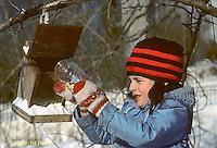BF01-006z  Bird feeder - girl putting seeds in feeder during winter