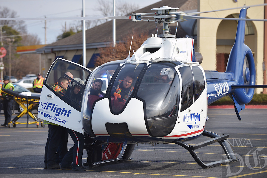 NWA Democrat-Gazette/BEN GOFF -- 02/26/15 Rogers first responders load a 31-year-old man with life-threatening injuries into a MedFlight helicopter in the parking lot of Frisco Station Mall after an accident on W. Walnut St. near the intersection with Dixieland Rd. in Rogers on Thursday Feb. 26, 2015. Four vehicles were involved in the accident that Keith Foster with the Rogers Police Department described as a chain reaction after a vehicle collided with cars stopped at the light. Four patients from one vehicle were transported by ambulance to Mercy Hospital and a 31-year-old man was flown to Washington Regional Medical Center by air ambulance with life-threatening injuries, according to the Rogers Fire Department.