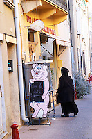 Gruissan village. La Clape. Languedoc. A hooded person dressed in black entering a butcher shop. Village street. France. Europe.
