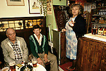 The Kings Head, High Ham, Langport, Somerset. UK Village pub 1980s. Landlady, Louisa May Brown (known as Maisie) and two locals. Maisie is scoring the darts match, note the dartboard scores in chalk on the  underside of the wooden flap leading into the bar.