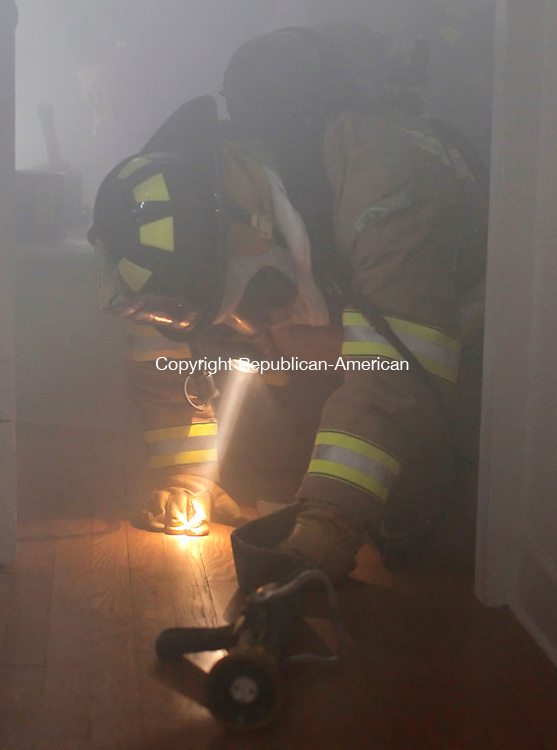 "Torrington, CT-16 February 2012-021612CM08-  Torrington firefighter, Michael Easter follows a hose line out of the room during a training exercise in an abandoned house on Summer St. Thursday afternoon in Torrington.  Easter along with fellow firefighter Brian Mazzarella  were being taught Self Containment Breathing Apparatus training (or SCBA) from Torrington Fire Department instructors.  The pair were subjected to a fog machine that simulated a real life smoke situation. ""It's a real life setting."" said Larry Hepburn, a department training officer.  The new firefighters were educated on how to use their air packs, locating mannequins using various techniques and learning controlled breathing techniques.  Today they will be learning water supply, which includes fire hydrants, drafting water from ponds and getting to know and the city's water system and how it works added Capt. Joseph McElroy.   Christopher Massa Republican-American"