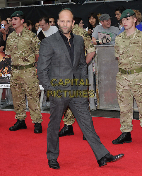 Jason Statham.'The Expendables 2' UK film premiere held at the Empire Leicester Square,.London, England..13th August 2012.full length hands in pockets black shirt grey gray suit stubble beard facial hair hands in pockets  .CAP/CAN.©Can Nguyen/Capital Pictures.